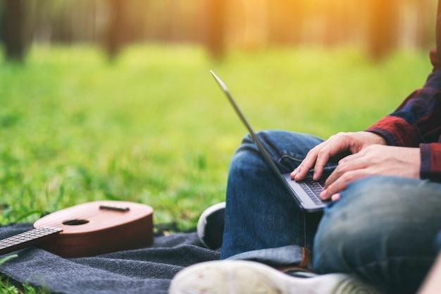公園に座ってノートパソコンのキーボードで作業し、入力している男性