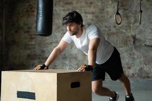 체육관에서 운동하는 남자는 나무 상자에서 팔 굽혀 펴기를합니다.