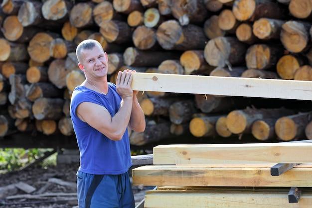 Мужчина работает с обработанными пиломатериалами на лесопилке