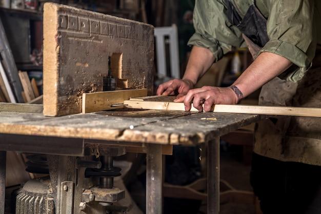 機械で木材製品を扱う男
