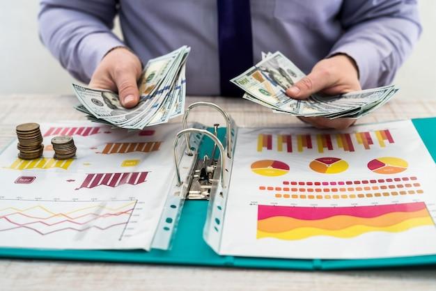 男性は、チャートやチャートドキュメント、ドル、ペニーを使用して、商品やサービス、オフィスの販売またはリースから会社の利益を計算します。事業分析と戦略の概念