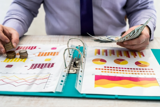 한 남자가 차트 및 차트 문서, 달러 및 동전을 사용하여 상품 또는 서비스 및 사무실의 판매 또는 임대로 인한 회사 수익을 계산하고 계산합니다. 비즈니스 분석 및 전략 개념