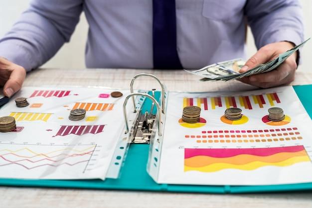 한 남자가 차트 및 차트 문서를 사용하여 상품 또는 서비스 및 사무실의 판매 또는 임대로 인한 회사 수익을 계산하고 계산합니다.