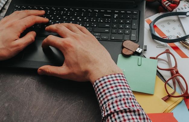 한 남자가 집이나 사무실에서 컴퓨터로 일하고 손으로 텍스트를 입력합니다.
