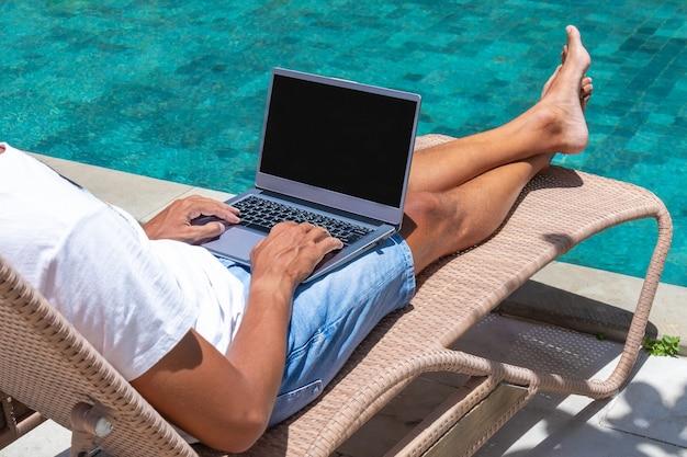 男はラップトップでプールのそばで働いています