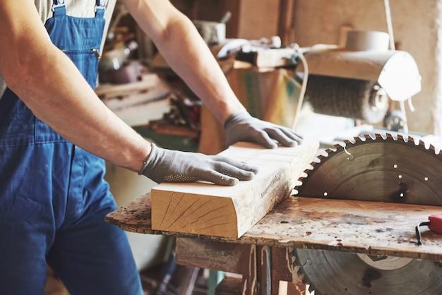 한 남자가 나무를 가지고 일하는 사람의 가게에서 일합니다.
