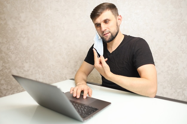 한 남자가 집에서 노트북으로 격리 작업을하고 의료용 마스크를 귀에 걸고 있습니다.