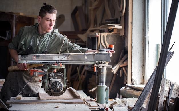 男は木製品で機械に取り組んでいます