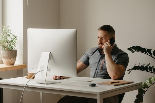 한 남자가 데스크톱 컴퓨터에서 원격으로 작업합니다. 집에서 화상 회의에서 동료의 보고 중에 수염을 기른 남자가 전화를 걸고 있습니다. 한 교사가 온라인 강의를 준비하고 있습니다.