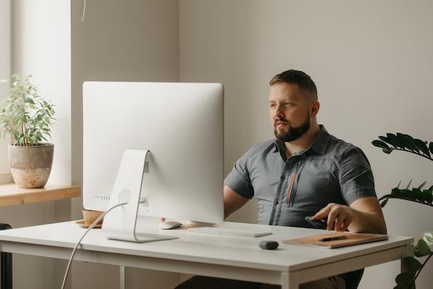 한 남자가 데스크톱 컴퓨터에서 원격으로 작업합니다. 수염을 기른 한 남자가 집에서 화상회의를 하고 있는 동료의 보고 중에 휴대폰을 내려놓고 있다. 한 교사가 온라인 강의를 준비하고 있습니다.