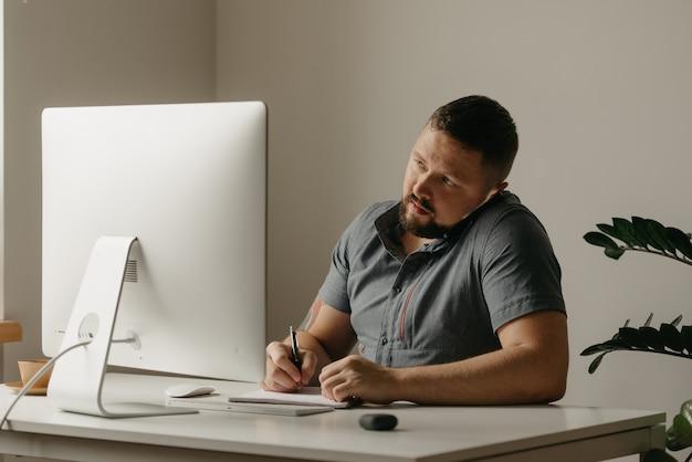 한 남자가 데스크톱 컴퓨터에서 원격으로 작업합니다. 수염을 기른 한 남자가 전화 통화 중에 메모를 하고 집에 있는 컴퓨터 디스플레이를 응시하고 있습니다. 한 교사가 온라인 강의를 준비하고 있습니다.