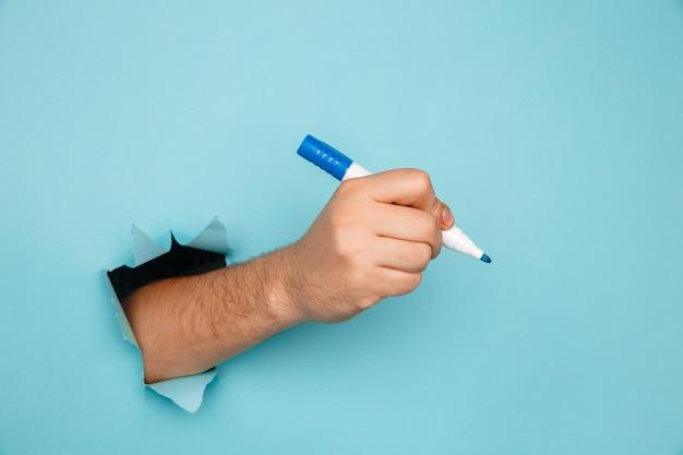 Мужчина пишет маркером на сломанной бумажной стене.