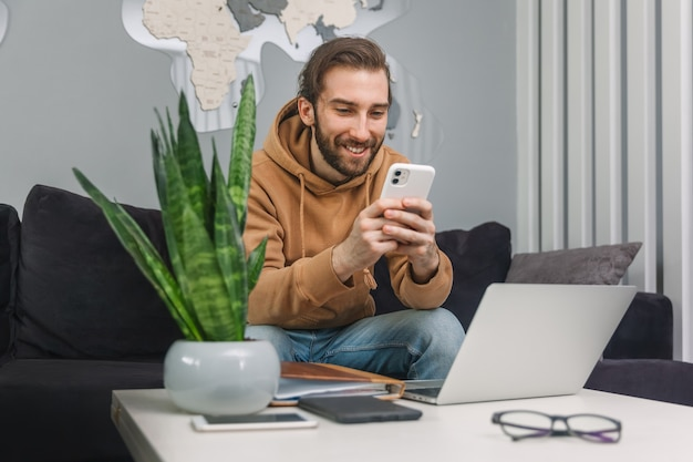 休憩中に男性が携帯電話にメッセージを書く