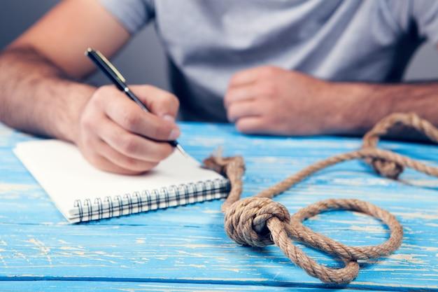 Мужчина пишет предсмертную записку. на столе есть петля