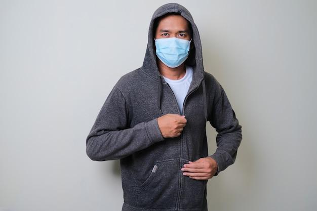 男はパーカーをジッパーで保護用の医療用マスクを着用しています