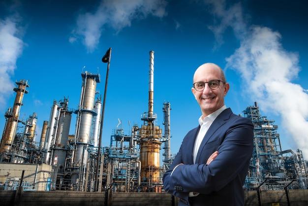 Менеджер улыбается на нефтеперерабатывающем заводе