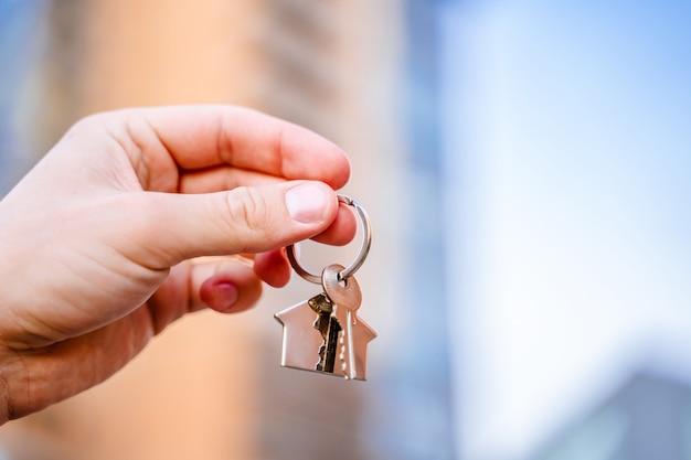 男の手が高層ビルを背景に新しい家の鍵を握る
