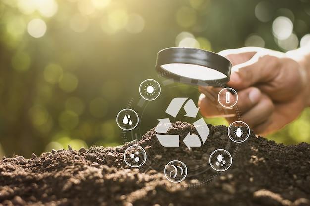 남자의 손은 물약을 사용하여 토양 순환에 대한 기술 아이콘으로 토양을 비 춥니 다.
