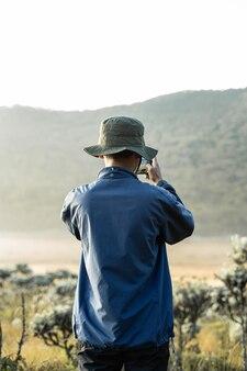 Манящая картина с мобильным телефоном в горах с туманом