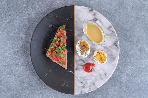 ゆで卵とトーストが入った大理石のプレート。高品質の写真