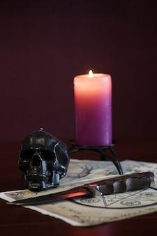 魔法のシンボルとシートの背景に栗色のキャンドルと頭蓋骨の形をしたキャンドル