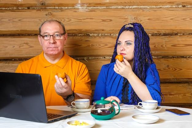 Супружеская пара мужчина в очках и женщина с голубыми косами афро за столом пьют чай с печеньем и работают за компьютером. горизонтальное фото