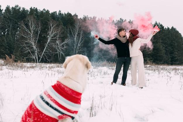 Супружеская пара в заснеженном лесу рядом со своей собакой держит в руках дымовые шашки