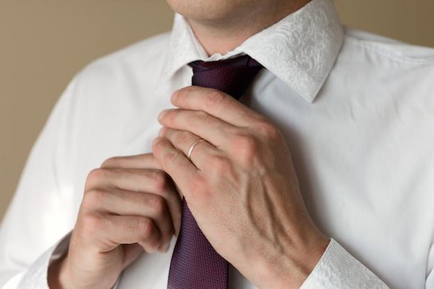 손에 반지가 달린 기혼 남성이 넥타이를 곧게 만듭니다.