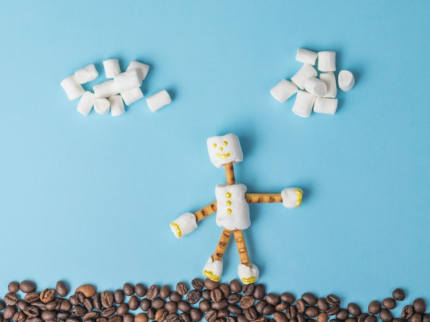 青い背景のコーヒー豆の上に立っているマシュマロの男。お菓子のコラージュ。フラットレイ。