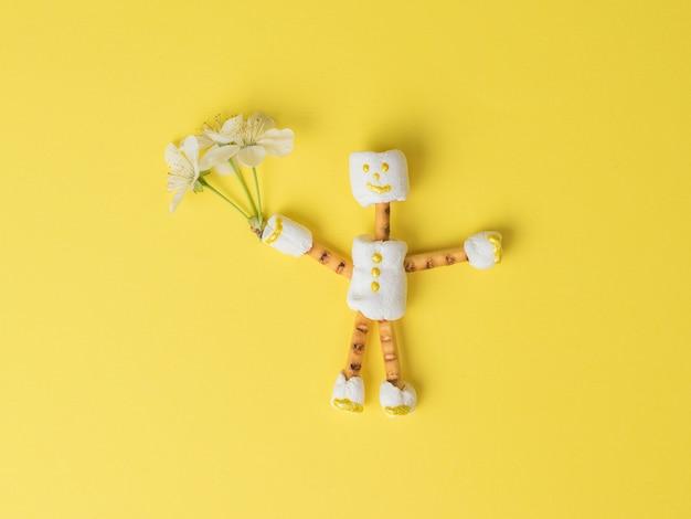 黄色の背景に彼の手に花束を持つマシュマロの男。お菓子のコラージュ。フラットレイ。