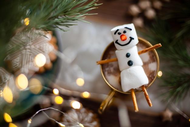 Снеговик из зефира, украшенный глазурью, золотая кружка с какао и рождественским декором имбирный пряник в ...