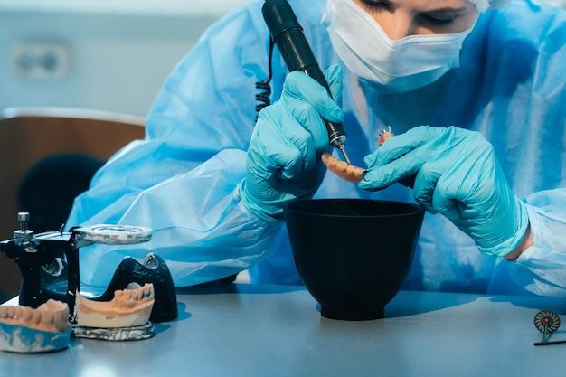 マスクをして手袋をはめた歯科技工士が、自分の研究室で義歯に取り組んでいます。