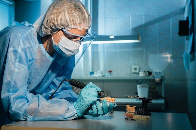 マスクをして手袋をはめた歯科技工士が、自分の研究室で義歯に取り組んでいます