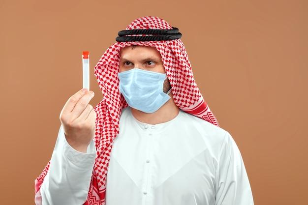 仮面をかぶったアラブ人が民族衣装を着た試験管を持っています。