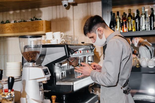 Бариста в маске готовит вкусный кофе в баре в кафе. работа ресторанов и кафе в период пандемии.