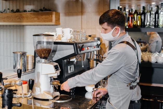 가면을 쓴 바리 스타가 카페의 바에서 맛있는 커피를 준비합니다. 대유행 기간 동안 레스토랑과 카페의 작업.