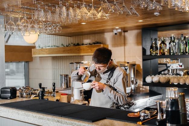 仮面のバリスタがカフェのバーで美味しいコーヒーを淹れる。パンデミック時のレストランやカフェの仕事。
