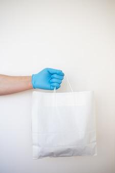 Доставщик в маске с перчатками держит крафт бумажный пакет с едой, изолированный