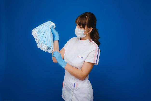 マスクされた医者は青い背景にマスクのセットを保持します