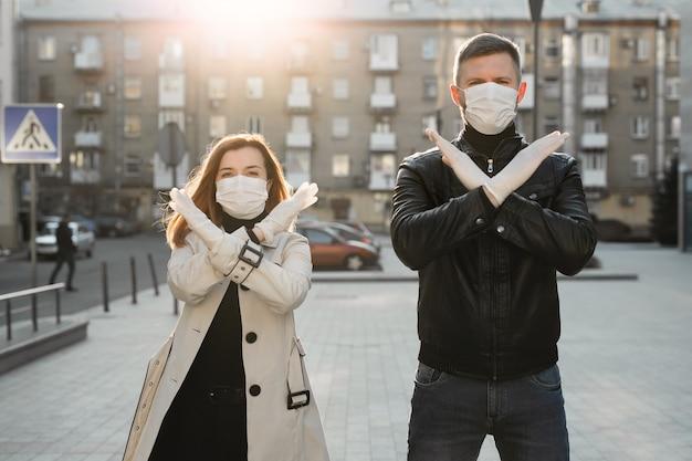 Мужчина и женщина в маске показывают знак остановки коронавируса. пандемия 2020 года. остановите коронавирус. covid-19. карантин. коронавирус вакцина