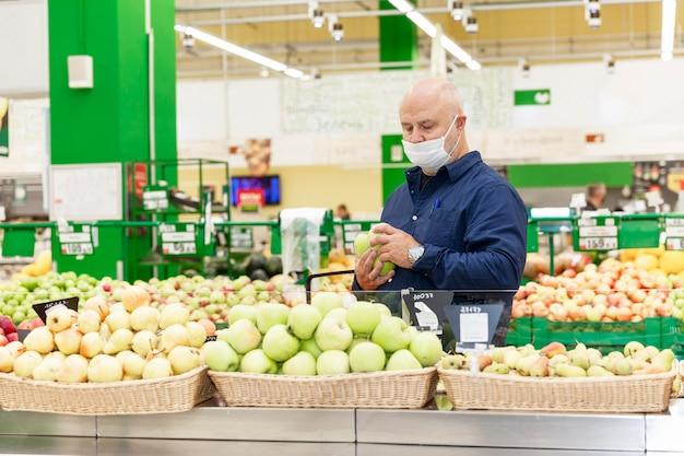 Мужчина в маске в супермаркете в отделе фруктов и овощей.
