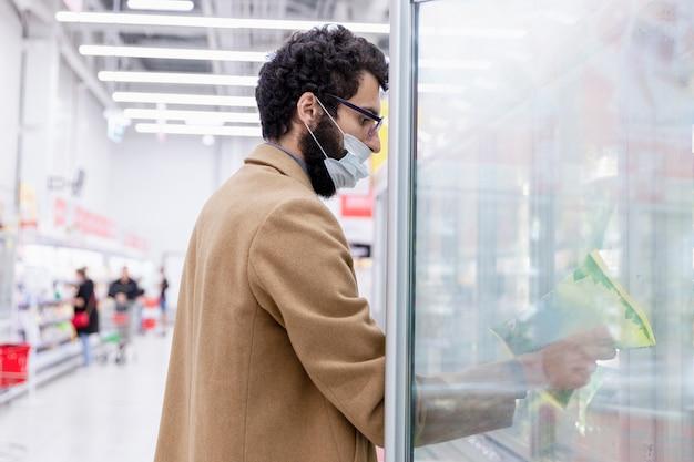 Мужчина в маске в отделе замороженных продуктов большого супермаркета. молодая брюнетка с бородой в бежевом пальто. коронавирус пандемия. вид сбоку.