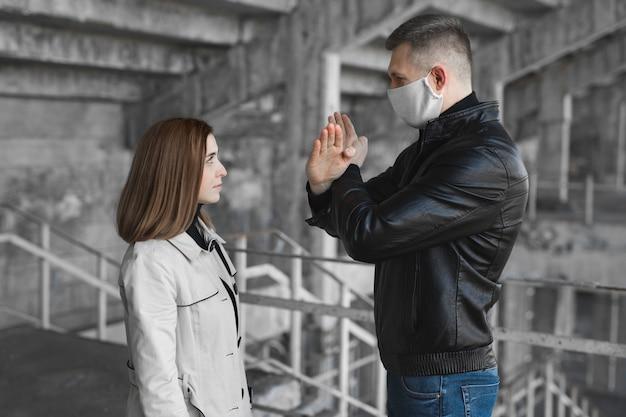 Мужчина в маске показывает женщине знак остановки коронавируса. пандемия 2020 года. останови ковид19. карантин. коронавирус вакцина.