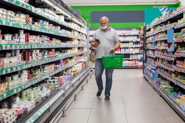 Мужчина в маске с телефоном в супермаркете ходит между полками с продуктами