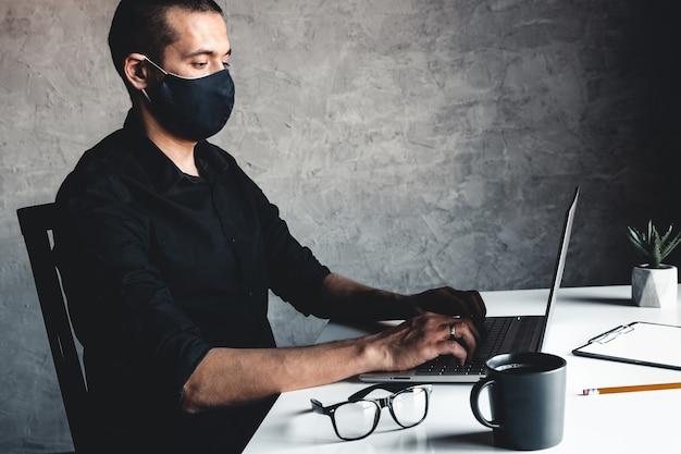 仮面の男がコンピューターで働いている。パンデミック、コロナウイルス、エピデミック