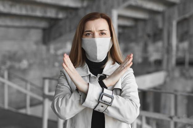Женщина в маске показывает знак остановки для коронавируса. пандемия 2020 года. останови ковид19. карантин. коронавирус.