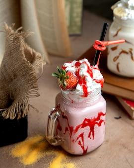 Мейсон баночка с клубничным молочным коктейлем с клубничным сиропом взбитыми сливками и клубникой