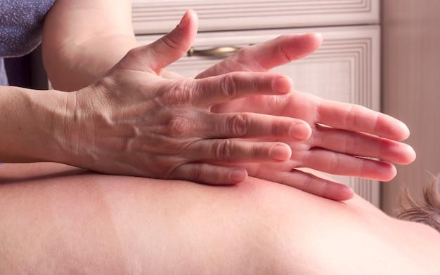 안마사는 여성에게 손바닥 가장자리로 두드리는 등을 마사지합니다.