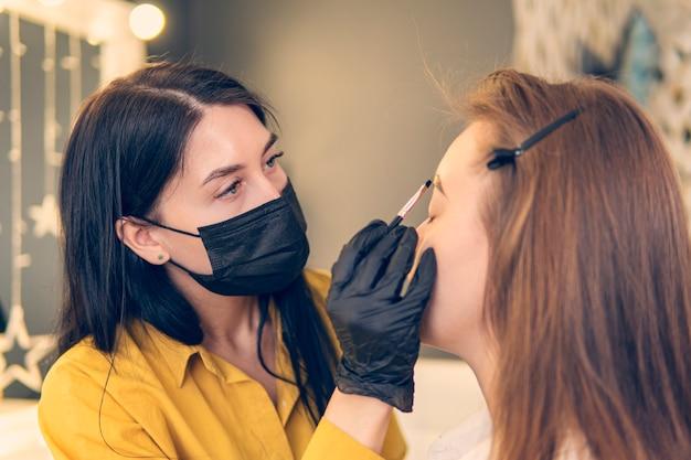 Мастер-косметолог закрашивает брови клиентки в салоне крупным планом. процедура окрашивания бровей, девушка вытирает краску с бровей.