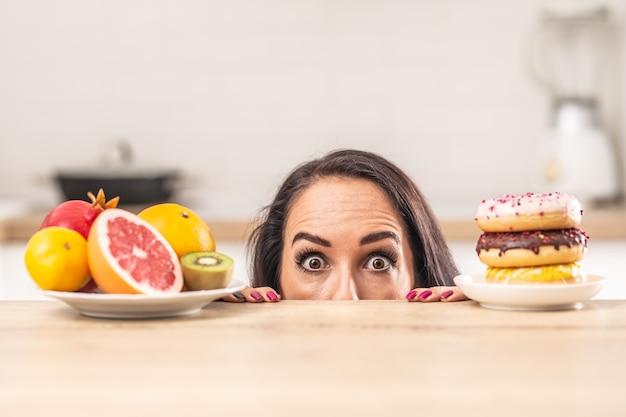果物とドーナツでいっぱいの皿が彼女の注意を引き付けようとするテーブルの上をのぞく女性のための選択の問題。